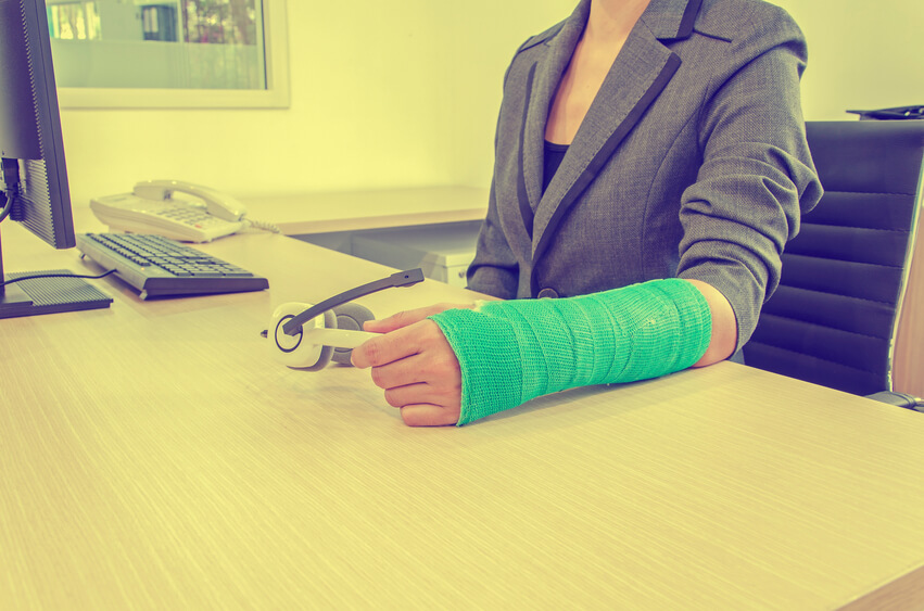 Image: Injured businesswoman with green cast on the wrist holding white headphones on wood table in office background