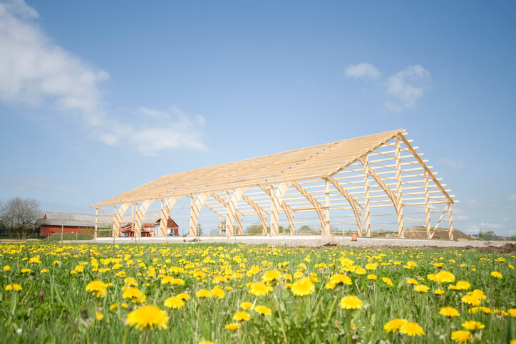 Image: Wooden frame of a barn under construction in a field