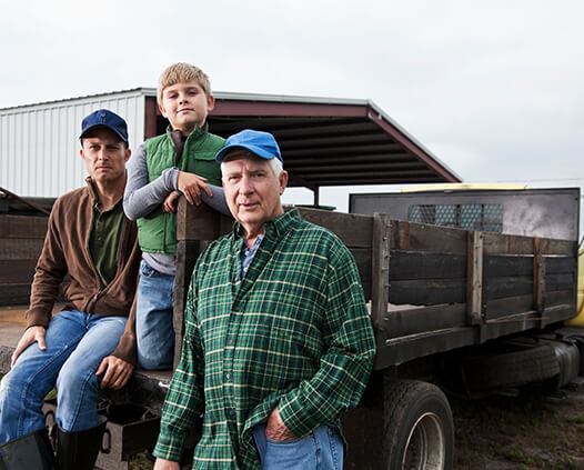 Image: three generations of farm workers posing with a truck