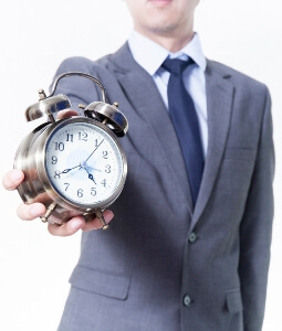 Image: Man in Business Suit holding a clock