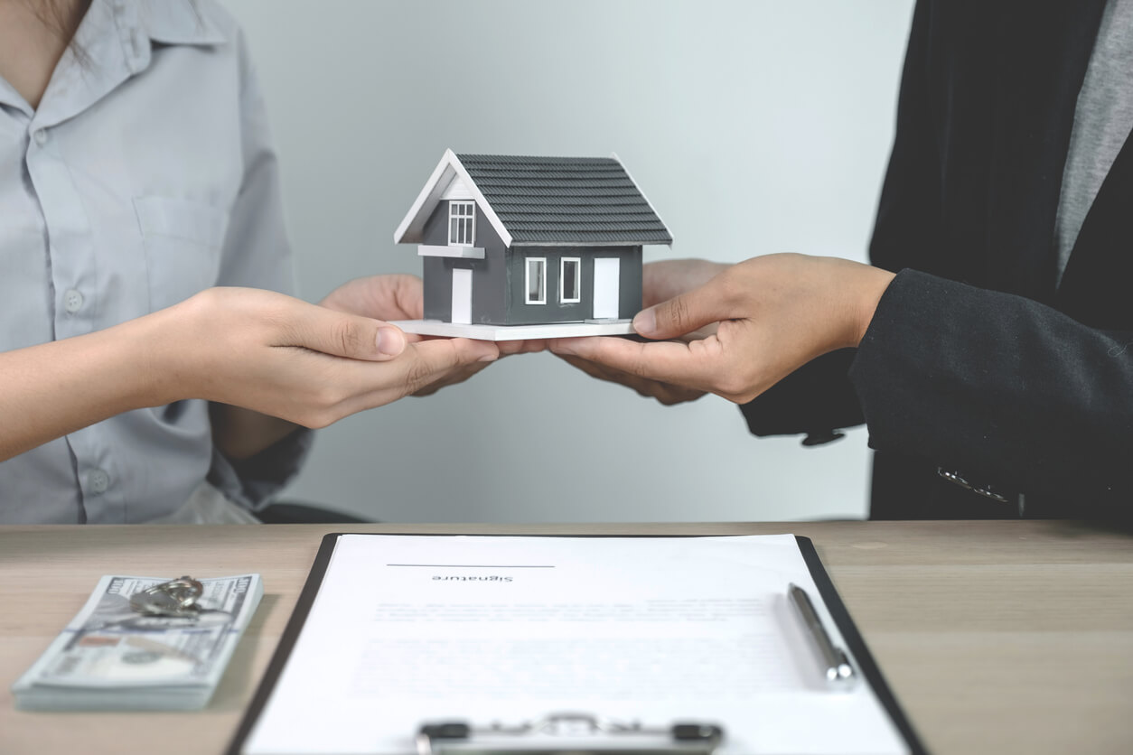 Image: two people holding a model of a house over a clipboard