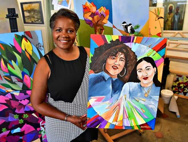 Image: Artist Ophelia Chambliss holding one of her paintings